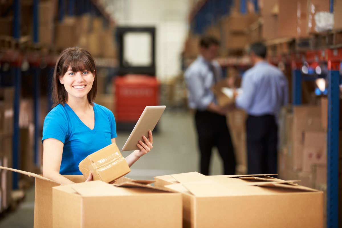 Woman scanning box in warehouse with mobile tablet
